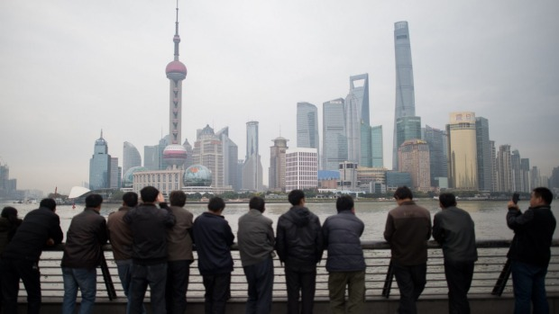 Chinese tourists stand along the promenade on the Bund overlooking the Huangpu River against the skyline of the Pudong ...