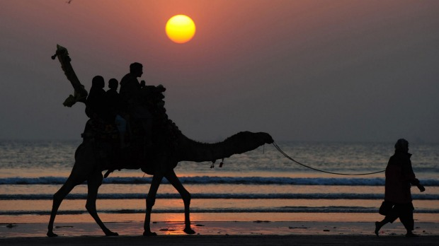 Pakistanis tourists ride on a camel during the last sunset of the year at Clifton beach in Karachi.