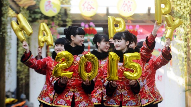 Guides in a Chinese park posing with balloons that read 'Happy 2015' to give out new year wishes to tourists at the park ...