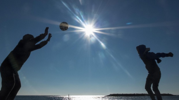 Tourists play with a ball on the beach on a sunny day at Valras-Plage, southern France.