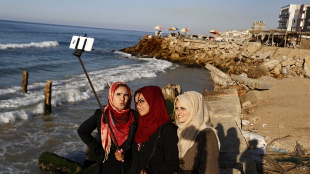 Palestinian girls take a group picture on the beach during the last day of 2014 off the coast of Gaza City.