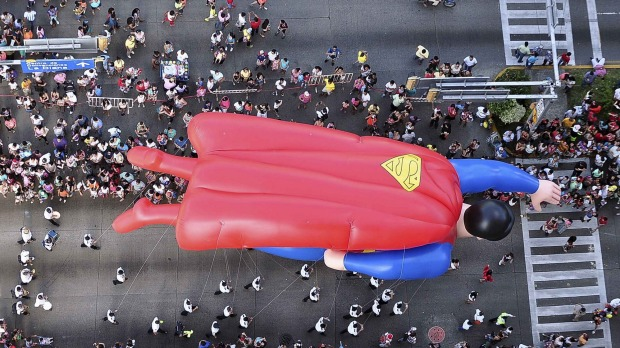 A balloon in the shape of comic hero Superman floats during a Christmas parade along the waterfront of the tourist ...