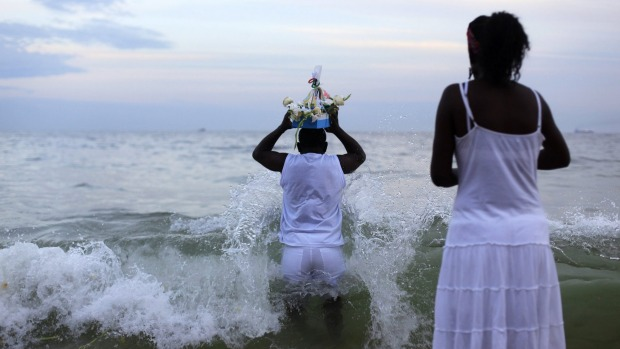 A follower of the Afro-Brazilian religion Umbanda carries offerings for Iemanja, goddess of the sea, in Copacabana Beach ...