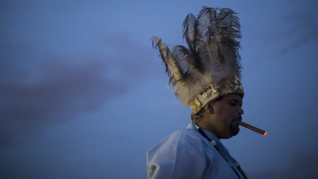 A man prays during a ceremony in honor of Iemanja, goddess of the sea, at Copacabana beach, in Rio de Janeiro, Brazil.