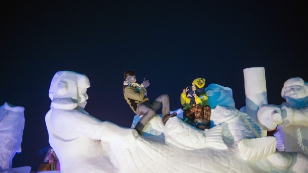 A couple takes pictures on a snow sculpture during the Harbin International Ice and Snow Festival in Harbin, northeast ...