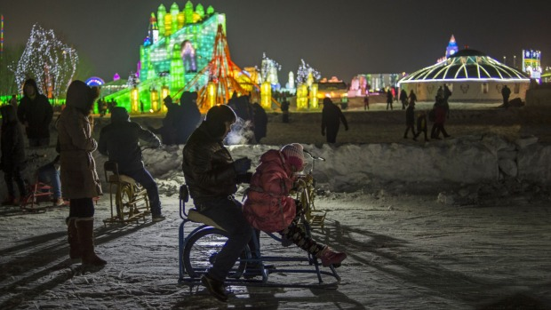 A father and his daughter ride a cycle over ice during the Harbin International Ice and Snow Festival in Harbin, ...