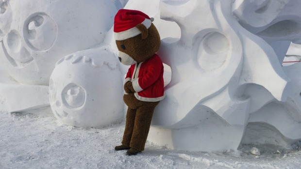 A man clad in a teddy bear suit leans on a snow sculpture during the Harbin International Ice and Snow Festival in ...