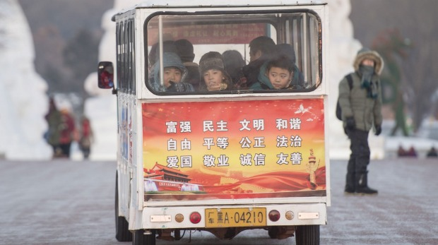 Children ride on a miniature bus during the Harbin International Ice and Snow Festival in Harbin, northeast China's ...