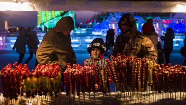 A child eyes fruit candy sticks during the Harbin International Ice and Snow Festival in Harbin, northeast China's ...
