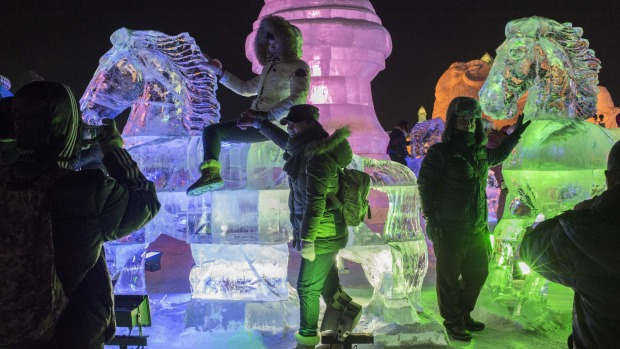 Visitors take photographs on an ice sculpture during the Harbin International Ice and Snow Festival in Harbin, northeast ...