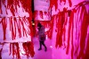 A woman looks for space to hang her red ribbon bearing her wish on an ice sculpture illuminated by coloured light during ...