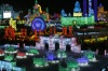 People visit ice sculptures illuminated by coloured lights during the opening day of the Harbin International Ice and ...