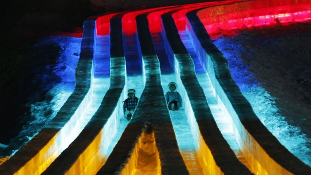 People ride slides on ice sculptures illuminated by coloured lights during the opening day of the Harbin International ...