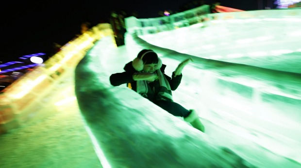 A woman rides a slide on ice sculptures illuminated by coloured lights during the Harbin International Ice and Snow ...