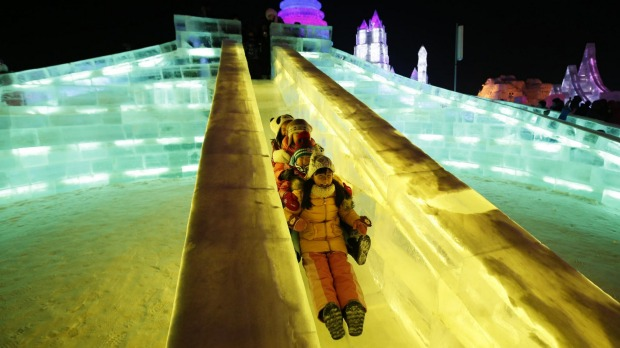 Children ride a slide on ice sculptures illuminated by coloured lights during the opening day of the Harbin ...