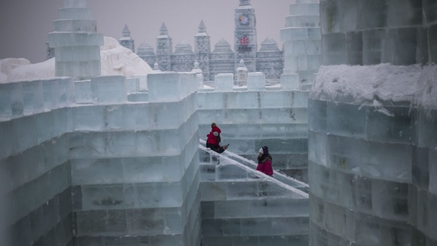 Visitors walk through an ice castle on the eve of the opening of the Harbin International Ice and Snow Festival in ...