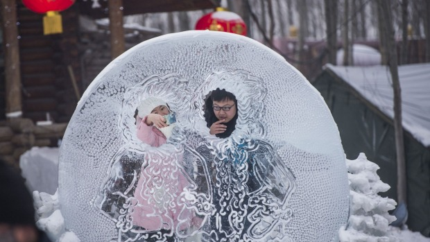 A couple poses at the China Ice and Snow World on the eve of the opening ceremony of the Harbin International Ice and ...