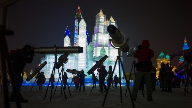 People look through telescopes of ice sculptures illuminated by coloured lights during the opening day of the Harbin ...