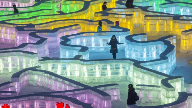 Visitors walk on an ice maze at the China Ice and Snow World during the Harbin International Ice and Snow Festival in ...