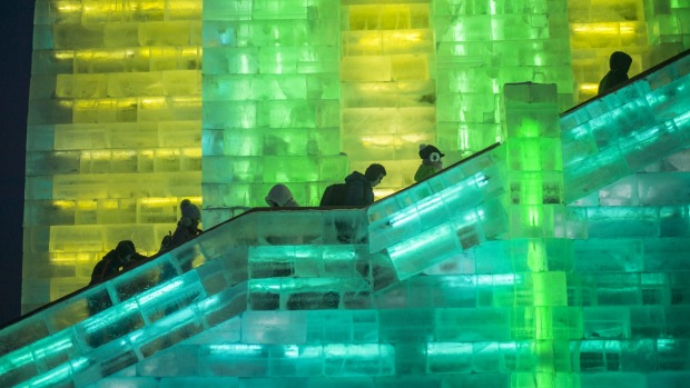 Visitors walks the stairs of an ice tower at the China Ice and Snow World on the eve of the opening ceremony of the ...