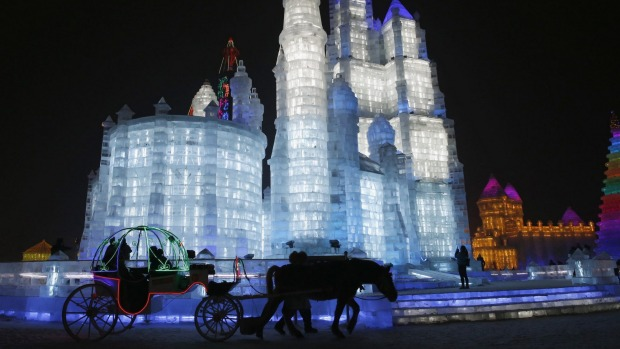 Tourists sit on a horse-drawn carriage in front of ice sculptures illuminated by coloured lights.