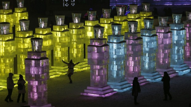 Visitors get a peak at ice sculptures are illuminated by coloured lights on the eve of the official opening of the festival.