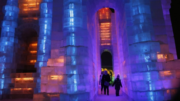 Ice sculptures illuminated by blue and purple coloured lights at the Harbin International Ice and Snow Festival in the ...