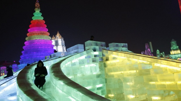 A man rides a slide on an ice sculpture illuminated by coloured lights on the eve of the opening ceremony of the Harbin ...