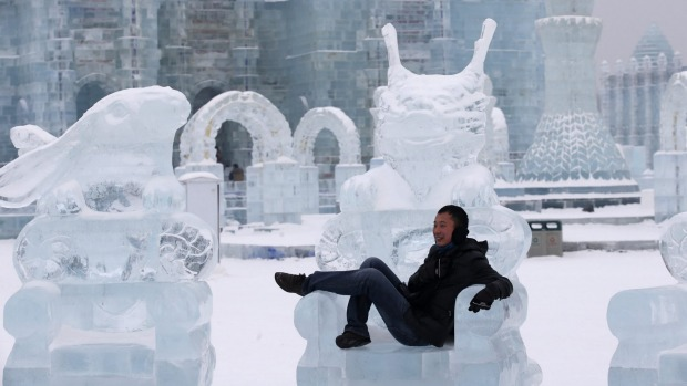 A visitor poses for a photo on a sculpture of a chair made from ice on the eve of the opening ceremony of the Harbin ...