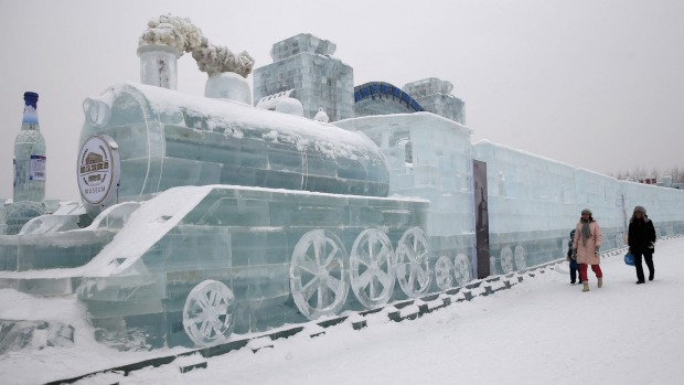 Visitors walk past a train-shaped ice sculpture.