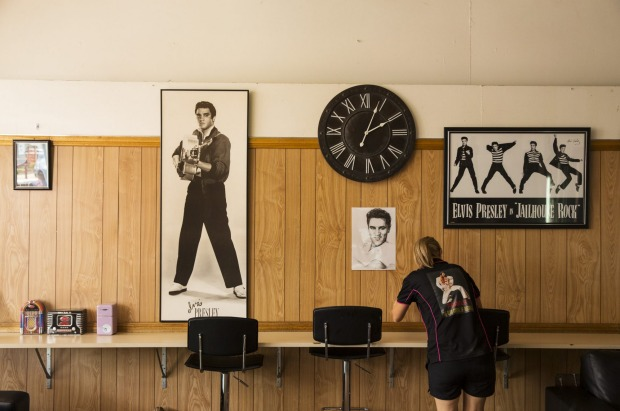 Employee cleaning up in a Bakery in Parkes with Elvis memrobillia on the walls during the Elvis festival.