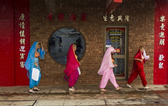 Ladies dressed up in an Elvis movie theme passing a Chinese restaurant on the main st in Parkes, Clarinda St whilst ...