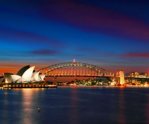 Two of Sydney's famous icons, the Sydney Opera House and Sydney Harbour Bridge lit up at dusk after a vivid sunset.