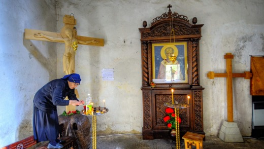 A nun lights candles inside the Church of the<br /> Assumption, Ananuri.