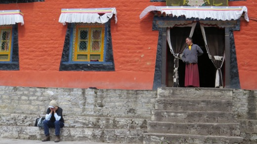 A monk looks at a trekker at Thame monastery.
