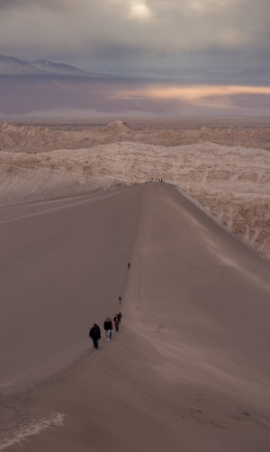 People hiking up a sand dune in Valle de la Luna.