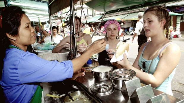 Tourists are served food from a street vendor on Khaosan Road.