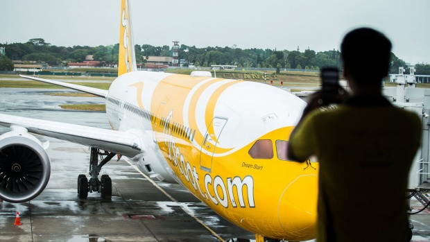 An employee of Scoot takes a photograph of a Boeing 787 Dreamliner aircraft as it sits on the tarmac at Changi Airport ...