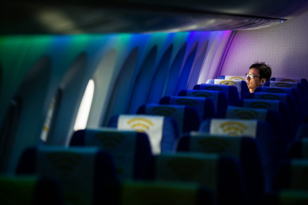 A man looks out of the window of a Boeing 787 Dreamliner aircraft operated by Scoot.