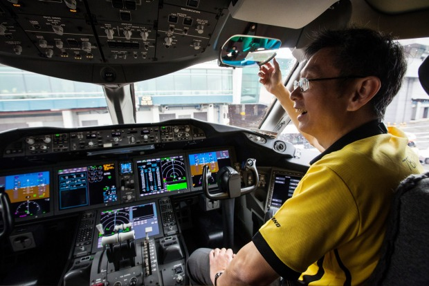 An employee sits in the cockpit of a Boeing 787 Dreamliner aircraft.