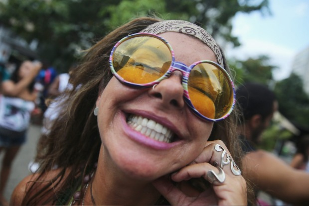 A reveller smiles while posing during a 'bloco' street parade during pre-Carnival festivities on February 7, 2015 in Rio ...