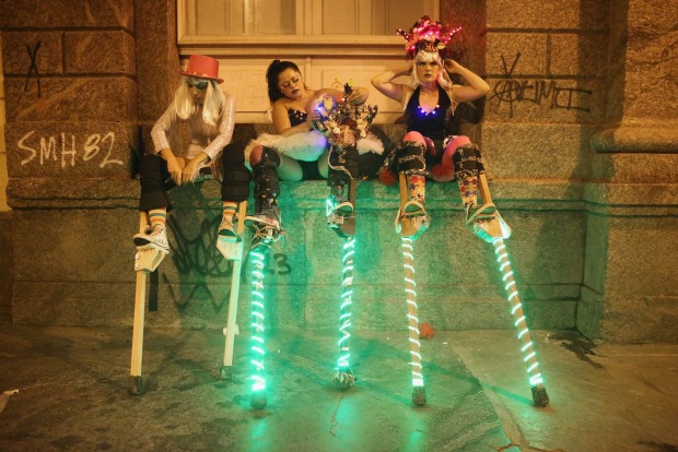 Stilt-walkers prepare to perform for revelers during the My Light is LED 'bloco' pre-Carnival street parade.
