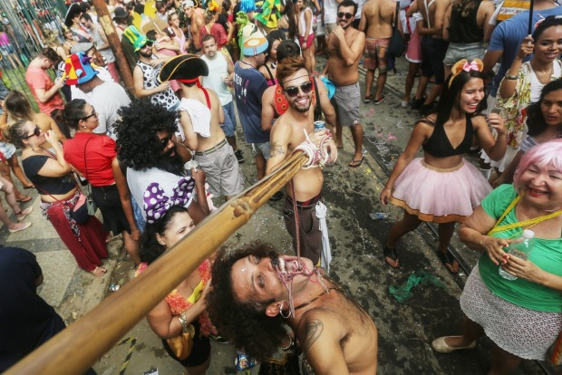 ReveLlers celebrate and clown around at the 'Ceu na Terra' (Sky on Earth) street parade during Carnival festivities in ...