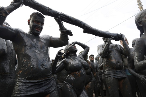 People covered in mud dance during the traditional 'Bloco da Lama' or 'Mud Block' carnival party, in Paraty, Brazil.