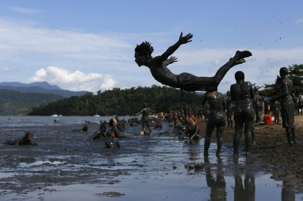 A man dives into a puddle mud during the traditional 'Bloco da Lama' or 'Mud Block' carnival party, in Paraty, Brazil. ...