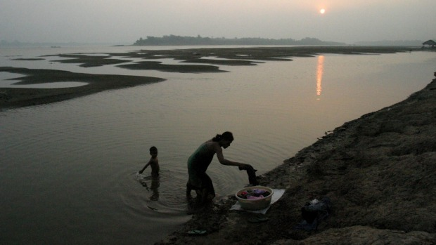 A Cambodian mother washes clothes as her son plays in the water on the Mekong river, 10km east of Phnom Penh.