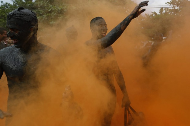 People covered in mud walk amid orange smoke during the traditional 'Bloco da Lama' or 'Mud Block' carnival party, in ...