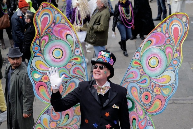 A person waves as the Rex parade rolls through on Mardi Gras in New Orleans. The crowd was thick along St. Charles ...