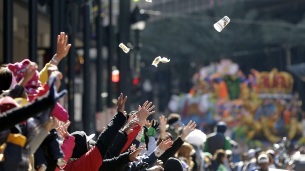People reach for beads and trinkets during the Krewe of Rex parade on Mardi Gras in New Orleans. Revellers in glitzy ...