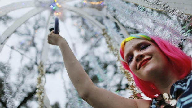 A member of the Krewe of Box of Wine makes her way down St. Charles Avenue in between Mardi Gras parades in New Orleans, ...